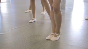 Στάση Ballerinas στο πάτωμα που καλύπτεται με το λινέλαιο φιλμ μικρού μήκους