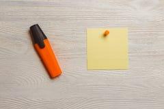 Στάσιμη, κενή κίτρινη αυτοκόλλητη ετικέττα, πορτοκαλί Pushpins, δείκτης στο λευκό ξύλινο πίνακα Υπόμνημα, υπενθύμιση Στοκ Φωτογραφίες
