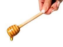 Στάλαγμα μελιού. Ξύλινο dipper μελιού στο θηλυκό χέρι που απομονώνεται στοκ φωτογραφία με δικαίωμα ελεύθερης χρήσης
