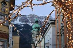 Στέγες του Ίνσμπρουκ με τα βουνά και των φω'των Χριστουγέννων σε ένα πρώτο πλάνο στο βράδυ στοκ φωτογραφία με δικαίωμα ελεύθερης χρήσης