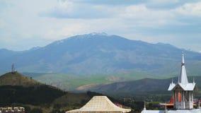 Στέγες των κτηρίων στο υπόβαθρο ενός χιονοσκεπούς βουνού φιλμ μικρού μήκους