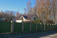 Στέγες των σπιτιών πίσω από το μεγάλο πράσινο φράκτη Στοκ εικόνα με δικαίωμα ελεύθερης χρήσης