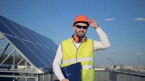 Στέγη με ένα ηλιακό πλαίσιο και έναν μηχανικό που ανυψώνουν hardhat του σε το απόθεμα βίντεο