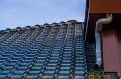Στέγη με τη μαύρη στιλπνή επικεράμωση στεγών και έναν σωλήνα αποχέτευσης, σύγχρονο ολλανδικό υπόβαθρο αρχιτεκτονικής στοκ εικόνα