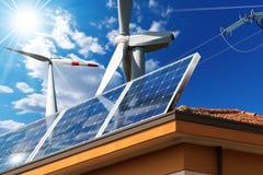 Στέγη σπιτιών με τα ηλιακά πλαίσια και τους ανεμοστροβίλους Στοκ εικόνες με δικαίωμα ελεύθερης χρήσης
