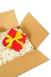Στέλνοντας κιβώτιο χαρτονιού, μικρό κόκκινο δώρο Χριστουγέννων μέσα, styrofoam κομμάτια συσκευασίας πολυστυρολίου Στοκ Εικόνες