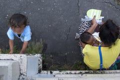 Στήθος γυναικών - που ταΐζει τα πωλώντας κεριά παιδιών στο ναυπηγείο εκκλησιών Στοκ Εικόνες