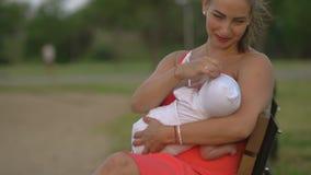 Στήθος - που ταΐζει: η νέα μητέρα θηλάζει το παιδί αγοράκι της στη συνεδρίαση πάρκων πόλεων σε έναν πάγκο που φορά το φωτεινό κόκ απόθεμα βίντεο