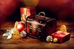Στήθος, δώρα και άλλη διακόσμηση Χριστουγέννων στον παλαιό ξύλινο πίνακα Στοκ Εικόνα