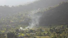 Στήλη του καπνού σε μια πράσινη κοιλάδα βουνών με τους τομείς ρυζιού και τα σπίτια απόθεμα βίντεο