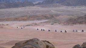 Στήλη των γύρων τετραγώνων ποδηλάτων μέσω της ερήμου στην Αίγυπτο στο σκηνικό των βουνών Οδήγηση ATVs φιλμ μικρού μήκους