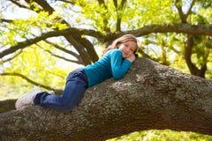 Στήριξη κοριτσιών παιδιών παιδιών που βρίσκεται σε έναν κλάδο δέντρων Στοκ φωτογραφία με δικαίωμα ελεύθερης χρήσης