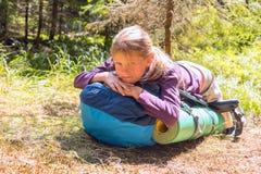 Στήριξη μικρών κοριτσιών, που βρίσκεται σε ένα σακίδιο πλάτης Στοκ φωτογραφία με δικαίωμα ελεύθερης χρήσης
