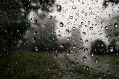 Σταγόνες βροχής κινηματογραφήσεων σε πρώτο πλάνο σε ένα παράθυρο στην επαρχία στοκ φωτογραφία