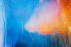 Σταγόνες βροχής σε ένα θολωμένο πολύχρωμο υπόβαθρο στοκ εικόνες