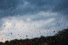 Σταγόνες βροχής σε ένα παράθυρο με το μπλε ουρανό Στοκ Εικόνες