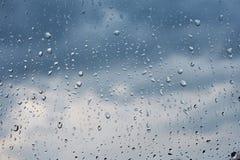 Σταγόνες βροχής σε ένα παράθυρο με το μπλε ουρανό Στοκ Φωτογραφία