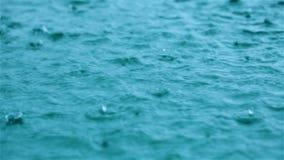 Σταγόνες βροχής στην επιφάνεια νερού απόθεμα βίντεο