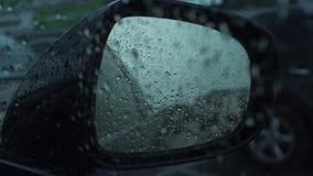 Σταγόνες βροχής στον οπισθοσκόπο καθρέφτη αυτοκινήτων Εκλεκτική εστίαση τονισμένος απόθεμα βίντεο