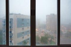 Σταγόνες βροχής στο αστικό σπίτι wndow κατά τη διάρκεια της βροχής Στοκ Εικόνες