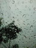 Σταγόνες βροχής στο γυαλί αυτοκινήτων με ένα γκρίζο υπόβαθρο ουρανού Στοκ Εικόνες