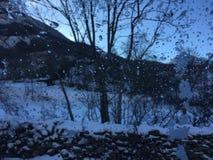 Σταγόνες βροχής στο γυαλί στο χειμερινό τοπίο στοκ εικόνες