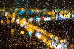 Σταγόνες βροχής στο γυαλί και τα φω'τα της πόλης τη νύχτα Στοκ φωτογραφία με δικαίωμα ελεύθερης χρήσης