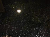 Σταγόνες βροχής στο παράθυρο θαμπάδων στη νύχτα πίσω από την επίδραση λαμπτήρων φωτισμού στοκ εικόνες