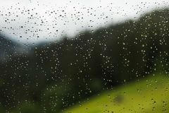Σταγόνες βροχής της βροχής στο γυαλί του παραθύρου του εξοχικού σπιτιού στην επαρχία α Στοκ εικόνες με δικαίωμα ελεύθερης χρήσης