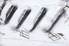 Σταθμευμένα αυτοκίνητα που καλύπτονται στο χιόνι μετά από τη τοπ άποψη χιονοθύελλας Στοκ Εικόνες
