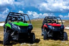 Σταθμευμένα ATV και UTV, buggies στην αιχμή βουνών με τα σύννεφα και το μπλε ουρανό στο υπόβαθρο Στοκ Φωτογραφία