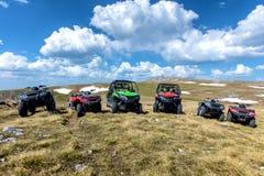 Σταθμευμένα ATV και UTV, buggies στην αιχμή βουνών με τα σύννεφα και το μπλε ουρανό στο υπόβαθρο Στοκ φωτογραφία με δικαίωμα ελεύθερης χρήσης