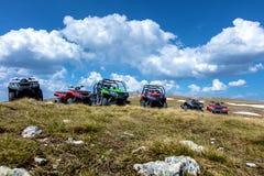 Σταθμευμένα ATV και UTV, buggies στην αιχμή βουνών με τα σύννεφα και το μπλε ουρανό στο υπόβαθρο Στοκ εικόνες με δικαίωμα ελεύθερης χρήσης