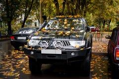 Σταθμευμένος αθλητισμός της Mitsubishi Pajero στα φύλλα σφενδάμου στοκ εικόνες