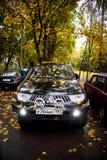 Σταθμευμένος αθλητισμός της Mitsubishi Pajero στα φύλλα σφενδάμου στοκ εικόνα