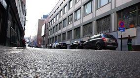 Σταθμευμένος στα περιθώρια και διάβαση των αυτοκινήτων κατά μήκος της οδού φιλμ μικρού μήκους