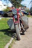 Σταθμευμένος στην παλαιά κόκκινη μοτοσικλέτα χορτοταπήτων στοκ φωτογραφία με δικαίωμα ελεύθερης χρήσης