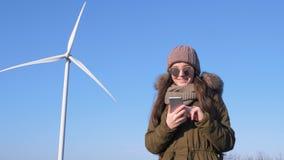 Σταθμός αιολικής ενέργειας, χαμογελώντας κορίτσι με το smartphone στα χέρια κοντά στον ανεμόμυλο ενάντια στον ουρανό σε υπαίθριο απόθεμα βίντεο