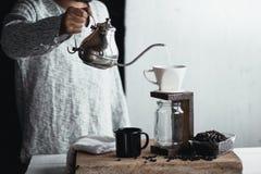 Σταλαγματιά καφέ, χέρι που κρατά έναν καφέ σταλαγματιάς κατσαρολών στο δωμάτιο στοκ εικόνα