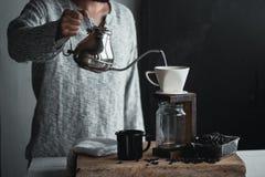 Σταλαγματιά καφέ, χέρι που κρατά έναν καφέ σταλαγματιάς κατσαρολών στο δωμάτιο στοκ εικόνες