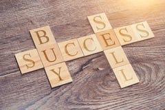Σταυρόλεξο των επιστολών νοοτροπίας επιτυχίας Αγοράστε και πωλήστε τις λέξεις σε ένα ξύλινο γραφείο στοκ εικόνες