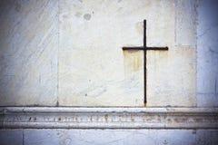 Σταυρός σιδήρου που αγκαλιάζει στοργικά στην άσπρη πέτρα σε μια ιταλική εκκλησία προσόψεων Στοκ Εικόνες