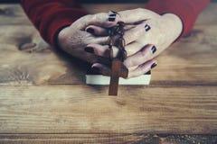 Σταυρός χεριών γυναικών με το βιβλίο στοκ εικόνες
