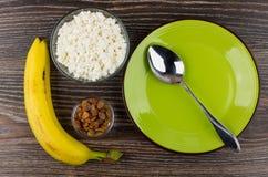 Σταφίδες, τυρί εξοχικών σπιτιών, κουτάλι στο πράσινο πιάτο και μπανάνα Στοκ φωτογραφίες με δικαίωμα ελεύθερης χρήσης