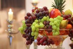 Σταφύλια, appels και αχλάδια σε ένα κύπελλο κοντά στα κεριά Στοκ Εικόνα