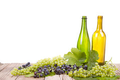 Σταφύλια και μπουκάλια στην ξύλινη σανίδα Στοκ Φωτογραφίες