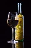 Σταφύλι και κρασί στο μαύρο υπόβαθρο Στοκ Εικόνες