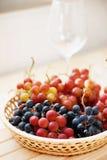 Σταφύλι στο ψάθινο καλάθι και τα κενά γυαλιά κρασιού Στοκ Φωτογραφίες