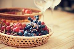 Σταφύλι στο ψάθινο καλάθι και τα κενά γυαλιά κρασιού Στοκ Εικόνες