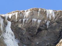 Σταλακτίτες πάγου και παγωμένος καταρράκτης σε ένα πρόσωπο βράχου Στοκ Φωτογραφία